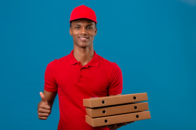 Young african american delivery man wearing red polo shirt and cap holding stack of pizza boxes projection thumbs up and smiling over isolated blue