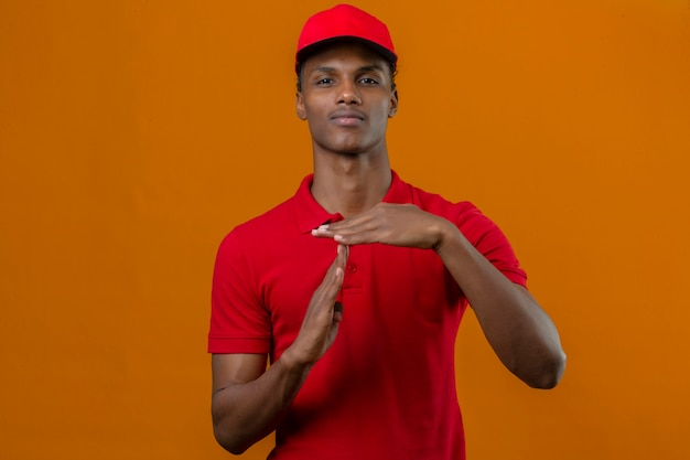 Young african american delivery man wearing red polo shirt and cap looking overworked montrant time out geste over isolated orange