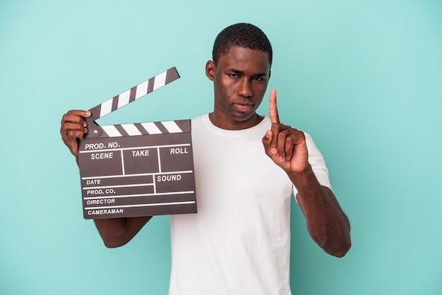 Young african american man holding clap isolé sur fond bleu montrant le numéro un avec le doigt.
