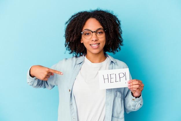 Young african american mixed race woman holding a help paper concept personne pointant à la main vers un espace copie de chemise, fier et confiant