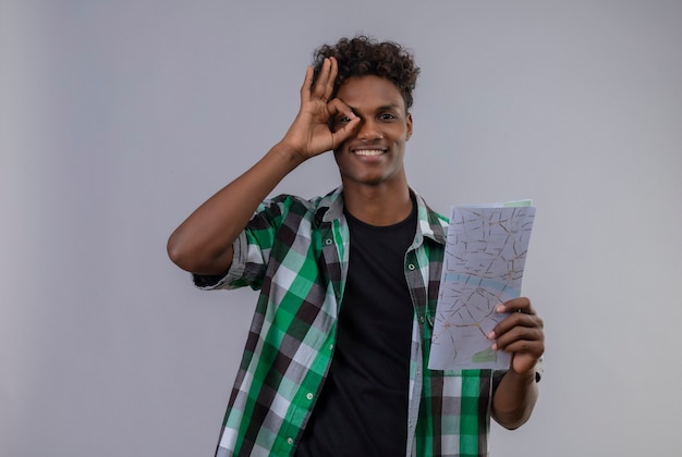 Young african american traveller man holding map smiling faisant signe ok regardant la caméra à travers ce signe debout sur fond blanc