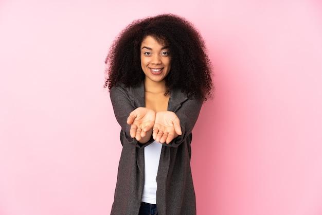 Young african american woman holding copyspace imaginaire sur la paume pour insérer une annonce