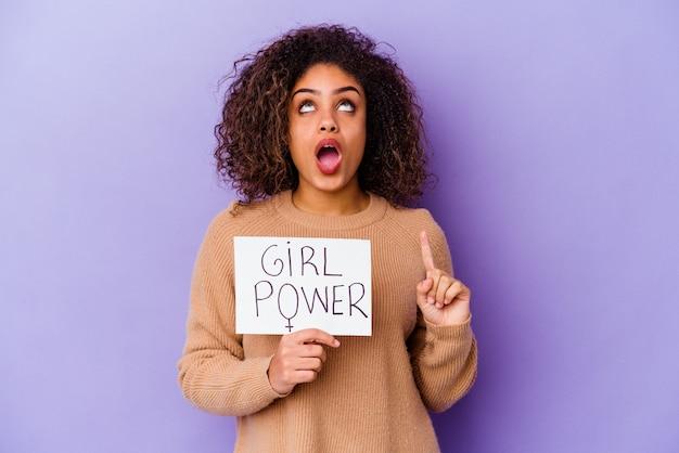 Young african american woman holding a girl power placard isolé sur mur violet pointant vers le haut avec la bouche ouverte