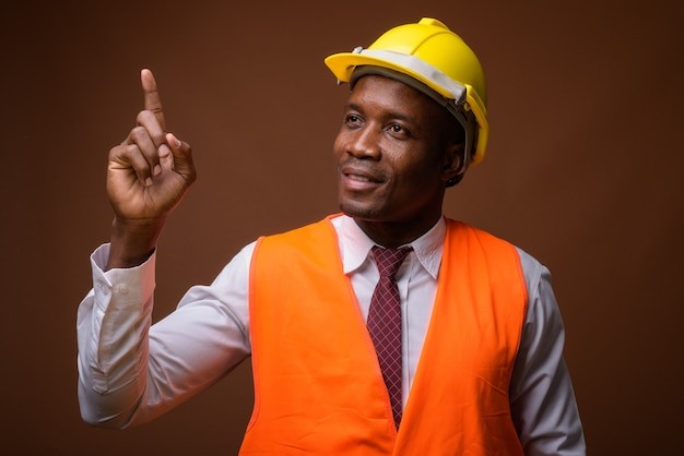Young african man construction worker sur fond marron