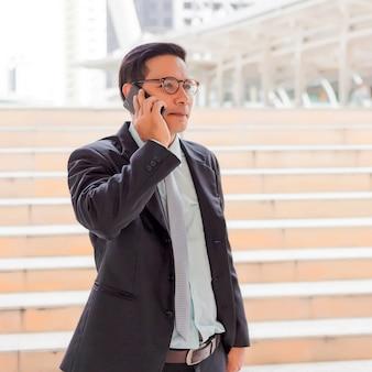 Young asia bel homme d'affaires avec son smartphone debout sur le trottoir de la ville moderne.