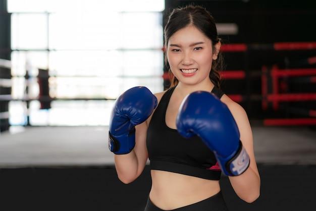 Young asian boxing fitness woman smiling happy portant des gants de boxe bleus