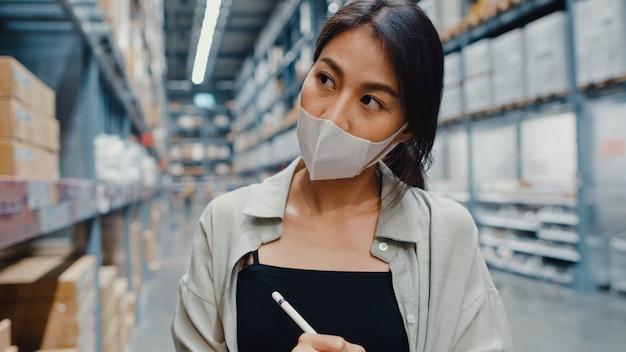 Young asian businesswoman manager portant entrepôt de masque facial à l'aide de la tablette numérique vérification de l'inventaire