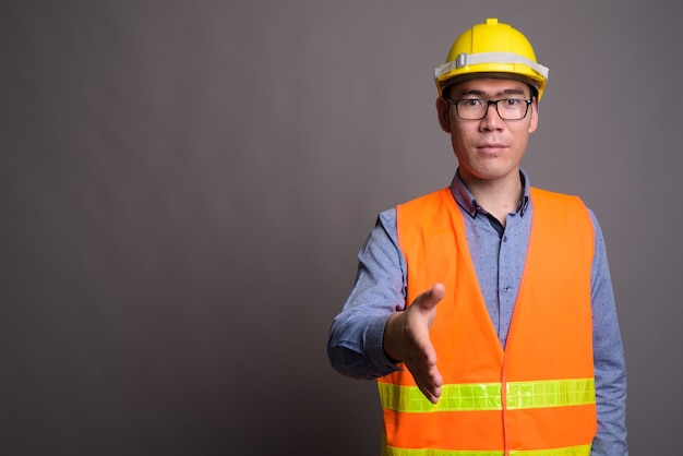Young asian man construction worker contre mur gris