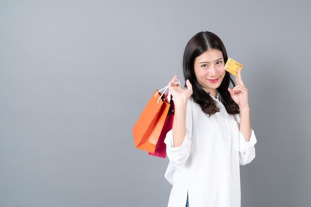 Young asian woman happy smiling holding carte de crédit et sacs à provisions en chemise blanche sur fond gris