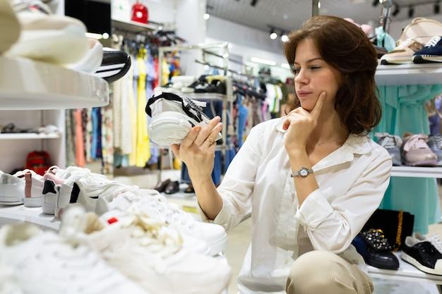 Young attractive female eyes musingly paire de chaussures dans le centre commercial
