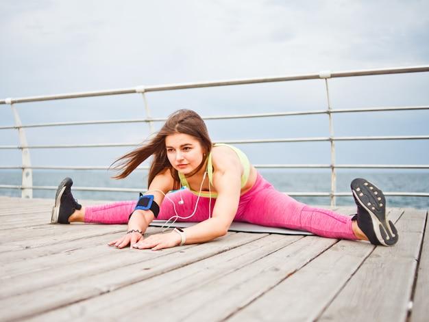 Young attractive fit woman doing stretching tout en étant assis sur un tapis sur la plage