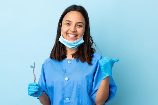 Young brunette mixed race dentist woman holding tools sur mur isolé avec les pouces vers le haut de geste et souriant