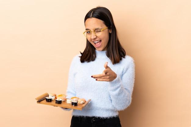 Young brunette mixed race woman holding sushi sur isolé pointant vers l'avant et souriant