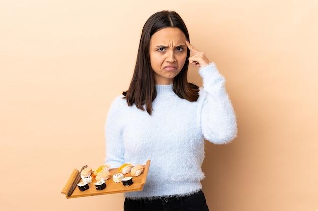 Young brunette mixed race woman holding sushi sur mur isolé pensant une idée