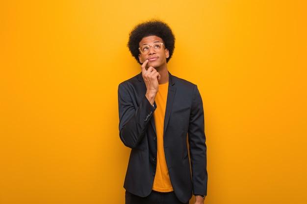 Young business african american man sur un mur orange doutant et confus