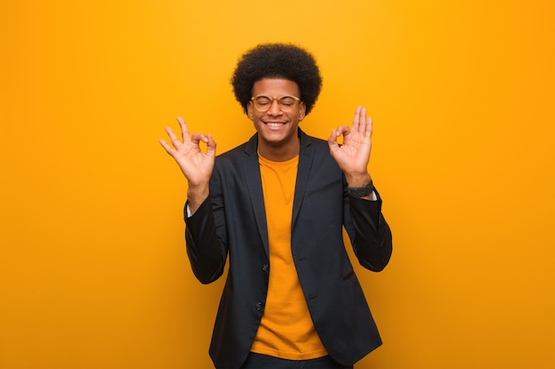 Young business african american man sur un mur orange effectuant le yoga