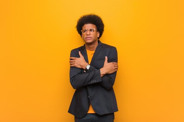 Young business african american man sur un mur orange va froid en raison de la basse température