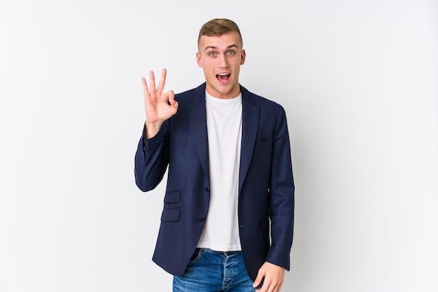 Young business caucasian man clin d'œil et détient un geste correct avec la main.