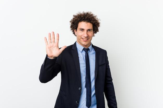Young business curly man smiling joyeux montrant le numéro cinq avec les doigts