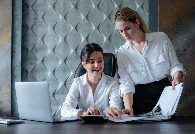 Young business lady female director sitting at office desk working process business meeting travaillant avec un collègue résolvant les tâches commerciales office concept collectif
