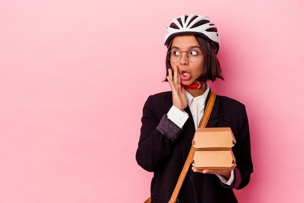 Young business mixed race woman wearing bike casque holding burger isolé sur mur rose dit un secret de freinage à chaud et à côté