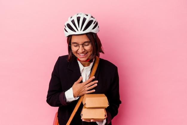 Young business mixed race woman wearing bike casque holding burger isolé sur mur rose en riant et en s'amusant