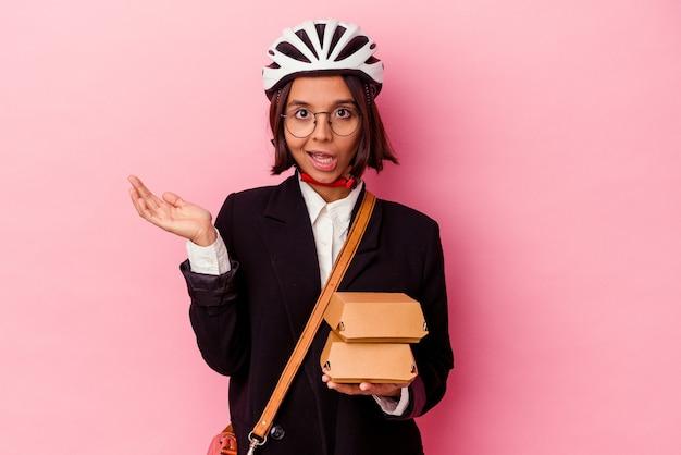 Young business mixed race woman wearing bike casque holding burger isolé sur mur rose surpris et choqué