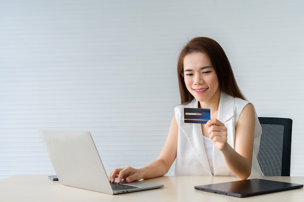 Young business woman holding carte de crédit et utilisant un ordinateur portable