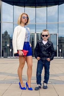 Young business woman in short blue malles debout et en attente d'une réunion de la banque de verre et son fils