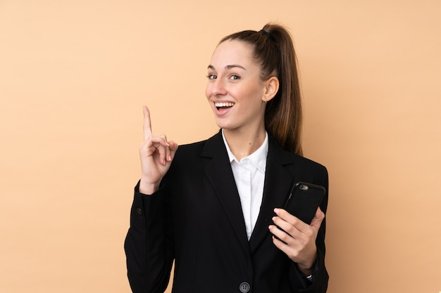 Young business woman using mobile phone over isolated wallpointing up a great idea