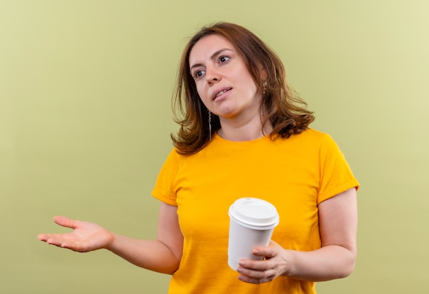 Young casual woman holding tasse à café en plastique et montrant la main vide regardant le côté gauche sur mur vert isolé