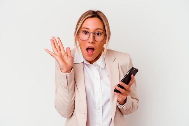 Young caucasian business woman holding mobile isolé sur blanc surpris et choqué.