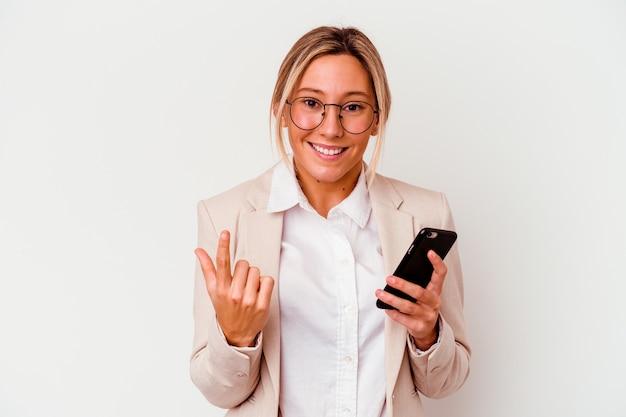 Young caucasian business woman holding mobile isolé sur un mur blanc pointant avec le doigt sur vous comme si vous invitiez à vous rapprocher.