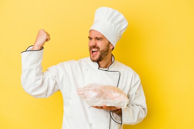 Young caucasian chef man holding chicken isolé sur mur jaune levant le poing après une victoire, concept gagnant.