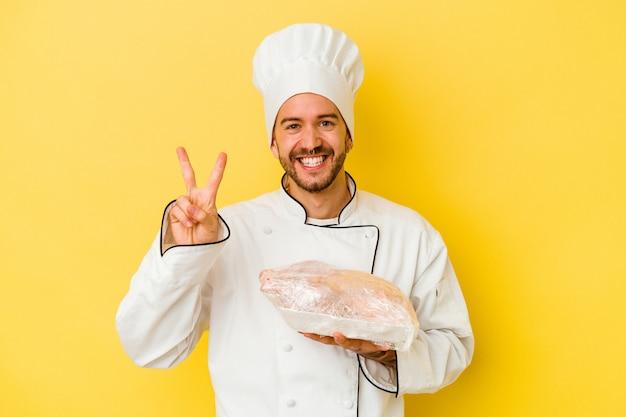 Young caucasian chef man holding chicken isolé sur mur jaune montrant le numéro deux avec les doigts.