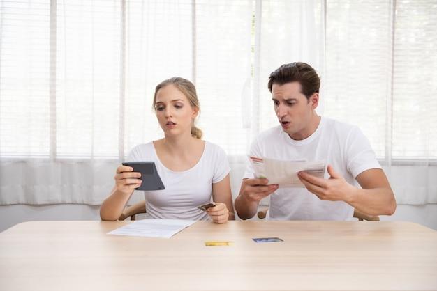 Young caucasian couple hand holding credit card et dette bill