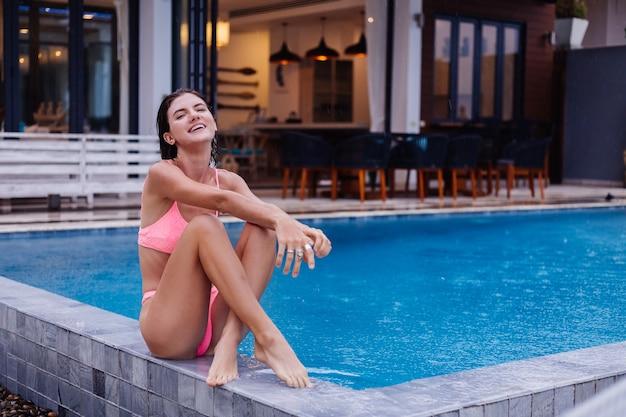 Young caucasian fit slim femme brune bronzée en bikini lumineux rose à l'extérieur de la villa