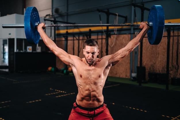 Young caucasian fitness boy dans la trentaine faisant push jerk dans une salle de sport