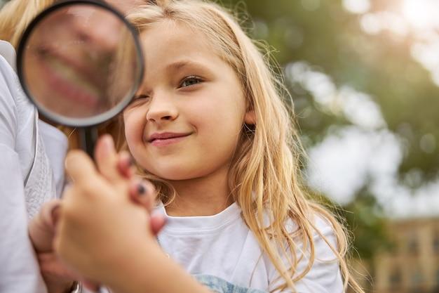 Young caucasian girl holding loupe à la main tout en regardant à travers elle