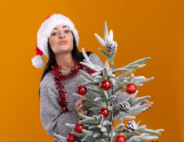 Young caucasian girl wearing christmas hat et guirlande de guirlandes autour du cou debout derrière l'arbre de noël décoré regardant la caméra faisant baiser geste isolé sur fond orange