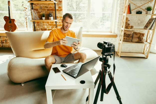 Young caucasian male blogger with professional camera record video review of tablet at home
