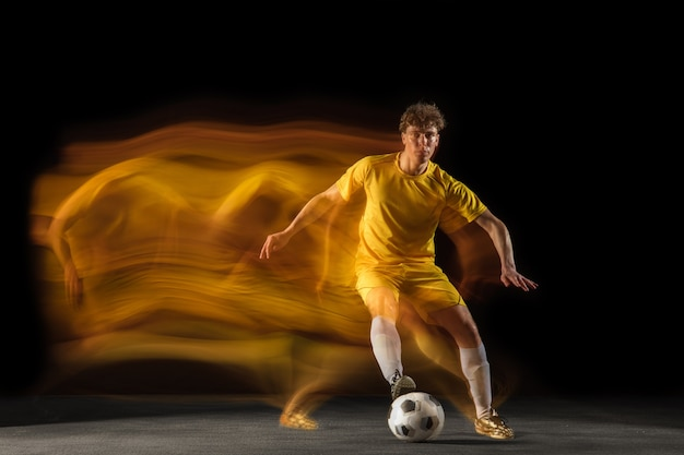 Young caucasian male football ou soccer player kick ball for the goal in mixed light on dark wall concept of healthy lifestyle professional sport hobby