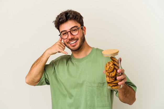 Young caucasian man holding cookies jar isolé sur fond blanc montrant un geste d'appel de téléphone portable avec les doigts.