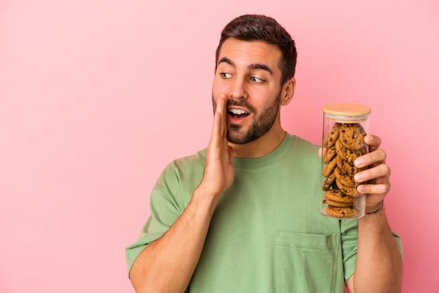 Young caucasian man holding cookies pot isolé sur fond rose dit un secret de freinage à chaud et à la recherche de côté