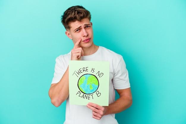 Young caucasian man holding a il n'y a pas de plaque-étiquette planète b isolé sur mur bleu