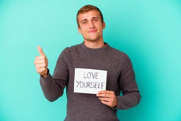 Young caucasian man holding a love yourself placard isolé sur fond bleu