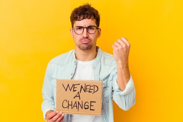 Young caucasian man holding a nous avons besoin d'une pancarte de changement montrant le poing, l'expression faciale agressive.