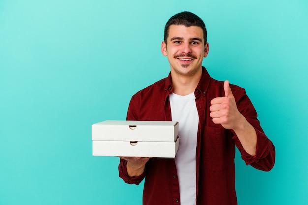 Young caucasian man holding pizzas isolé sur mur bleu souriant et levant le pouce vers le haut