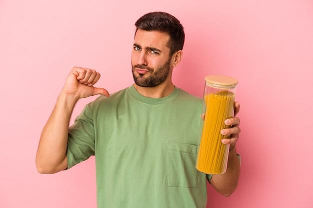 Young caucasian man holding pot de pâtes isolé sur mur rose se sent fier et confiant, exemple à suivre