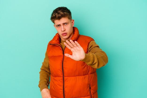 Young caucasian man isolated on blue wall étant choqué en raison d'un danger imminent
